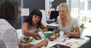 Three Businesswomen Having Working Lunch In Office