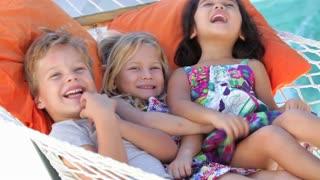 Three Children Relaxing In Garden Hammock Together