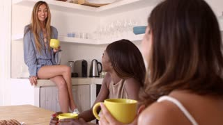 Three female friends drinking coffee and talking in kitchen, shot on R3D
