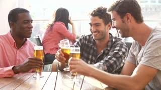 Three Male Friends Enjoying Drink At Outdoor Rooftop Bar