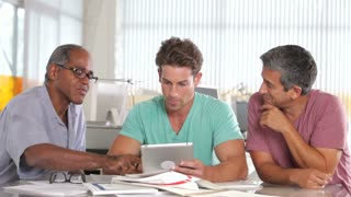 Three Men Using Tablet Computer In Creative Office