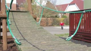 Three Schoolboys Playing On Climbing Equipment