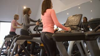 Three woman exercise on equipment at a gym, low angle