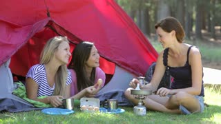 Three Women Cooking Breakfast On Camping Holiday Together