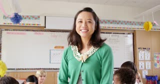 Tilt shot of female Asian school teacher in front of class