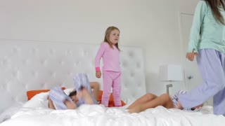 Time Lapse Sequence Of Four Children Playing On Bed