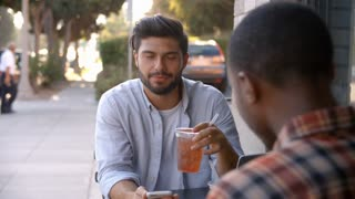 Two adult male friends talking over cold drinks outside cafe