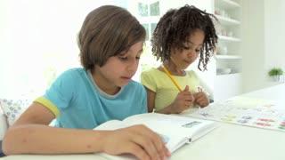 Two African American Children Doing Homework In Kitchen