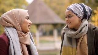 Two British Muslim Women Meeting In Urban Park
