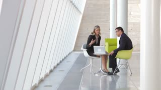 Two Business People With Laptop Having Meeting