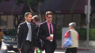 Two Businessmen Chatting Walking Along Street