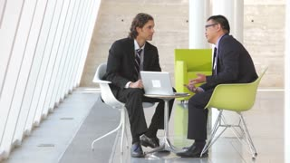 Two Businessmen With Laptop Having Meeting