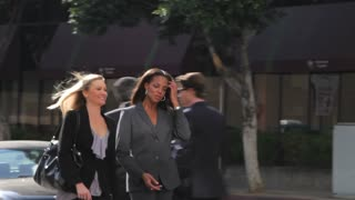 Two Businesswomen Chatting Walking Along Street