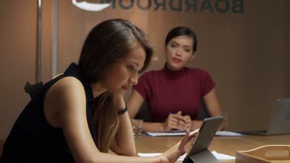 Two businesswomen working late using tablet computer, rack focus shot on R3D