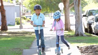 Two Children Riding Scooters Towards Camera