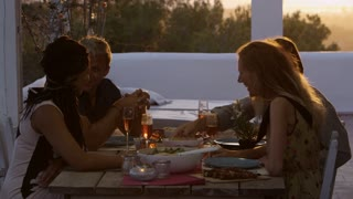 Two couples eating dinner at a table on a rooftop terrace, shot on R3D