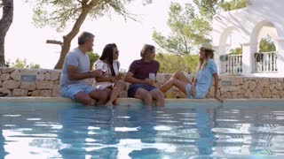 Two couples sit at poolside talking, front view, shot on R3D
