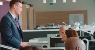 Manager walking through open plan office talking to staff