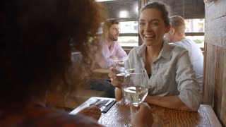 Two female friends having a drink at a table in a bar