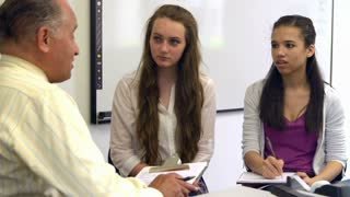 Two Female Students Talking To High School Counselor
