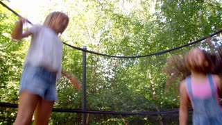 Two Girls Jumping On Trampoline Shot In Slow Motion