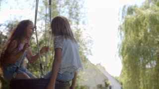 Two Girls Playing On Tire Swing In Garden