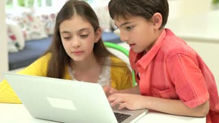 Two Hispanic Children Using Laptop At Home