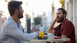 Two male friends talking at a table outside a cafe, Ibiza