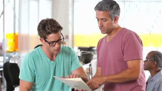Two Men Discussing Document In Creative Office