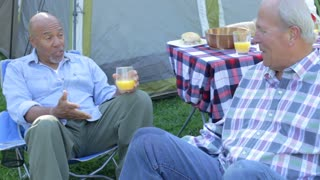 Two Senior Men On Camping Holiday Set Off On Fishing Trip