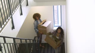 Two Women Moving Into New Home Carrying Box Upstairs