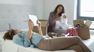 Two Women Moving Into New Home Using Digital Tablet
