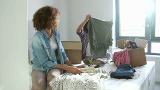 Two Women With Boxes In Bedroom Moving Into New Home