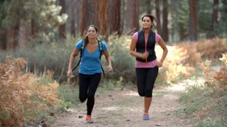 Two young women running in a forest, close up