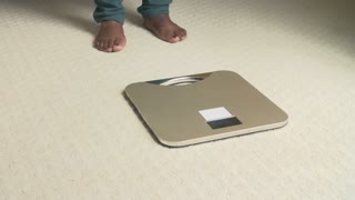 Unhappy Overweight Woman Weighing Herself On Scales