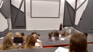 University lecture in lecture theatre, back row student POV