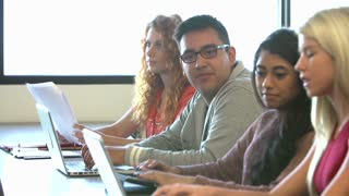 University Students Using Digital Tablet And Laptop In Class