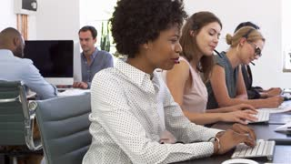 A row of women using phone headsets in an open plan office