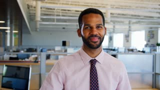 A young Black businessman smiles in an open plan office