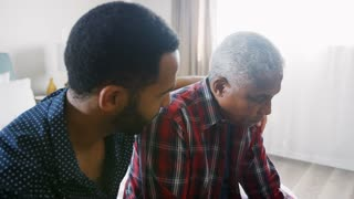 Adult Son Comforting Senior Father Suffering With Depression At Home