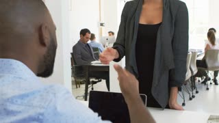 Asian woman greeting a man at a meeting in a busy office