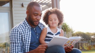 Black father and young daughter reading a book outdoors