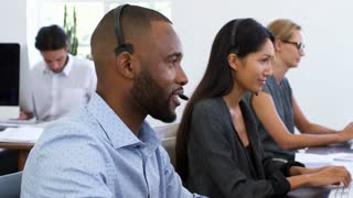Black man in headset smiles to camera in open plan office