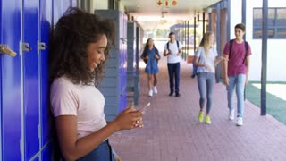 Black teenage girl using smartphone in school corridor