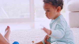 Black toddler boy playing xylophone with mum in sitting room