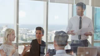 Businessman Leads Meeting Around Table Shot Through Door