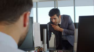 Businessman Making Phone Call Standing At Desk In Office