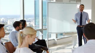 Businessman Making Presentation To Colleagues In Office
