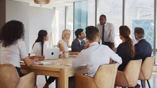Businessman Stands To Address Meeting Around Board Table