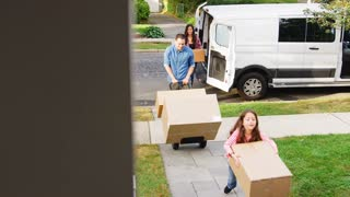 Child Helping Unload Boxes From Van On Family Moving In Day